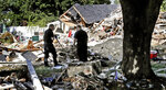 FILE- In this Sept. 21, 2018 file photo, fire investigators pause while searching the debris at a home which exploded following a gas line failure in Lawrence, Mass. Federal investigators are confirming that over pressurized natural gas lines were the source of a series of explosions and fires in communities north of Boston last month. The preliminary report on Thursday, Oct. 11 from the National Transportation Safety Board said that Columbia Gas work in Lawrence on Sept. 13 failed to account for the location of critical gas pressure sensors, causing high-pressure gas to flood the distribution system at excessive levels. (AP Photo/Charles Krupa, File)
