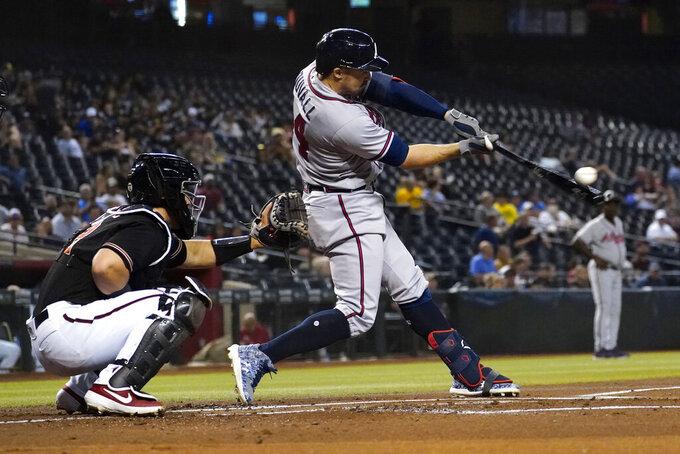Atlanta Braves' Adam Duvall connects for a two run home run against the Arizona Diamondbacks during the first inning of a baseball game, Wednesday, Sept. 22, 2021, in Phoenix. (AP Photo/Matt York)