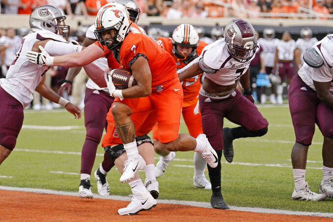 Oklahoma State running back Jaylen Warren runs into the end zone for a touchdown past Missouri State linebacker Titus Wall, right, in the first half of an NCAA college football game, Saturday, Sept. 4, 2021, in Stillwater, Okla. (AP Photo/Sue Ogrocki)
