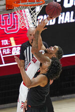 Utah forward Timmy Allen (1) shoots as Oregon State guard Ethan Thompson, foreground, defends during the second half during an NCAA college basketball game Wednesday, March 3, 2021, in Salt Lake City. (AP Photo/Rick Bowmer)
