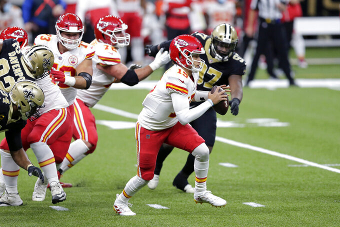 Kansas City Chiefs quarterback Patrick Mahomes (15) scrambles past New Orleans Saints defensive tackle Malcolm Roach (97) in the first half of an NFL football game in New Orleans, Sunday, Dec. 20, 2020. (AP Photo/Brett Duke)