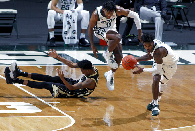 Michigan State's Rocket Watts, right, starts a fast break after a steal against Western Michigan's Jaylon Holmes, left, as Michigan State's Aaron Henry, center, trails during the first half of an NCAA college basketball game, Sunday, Dec. 6, 2020, in East Lansing, Mich. (AP Photo/Al Goldis)