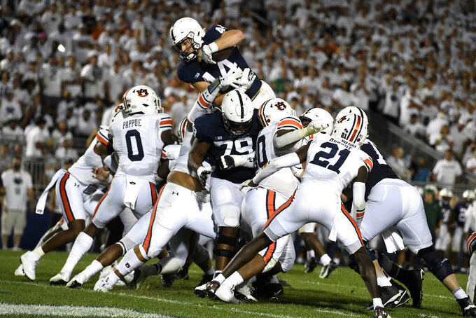 Penn State's Tyler Warren (44) dives over Auburn linebacker Owen Pappoe (0) to score during the second half of an NCAA college football game in State College, Pa., on Saturday, Sept. 18, 2021. (AP Photo/Barry Reeger)