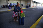 Hurricane Dorian evacuee Kennecia Burrows, 11, pushes her 3-year-old cousin, Trevanti Saunders both of Freeport, across the street as he sits on a suitcase after arriving on the Grand Celebration cruise ship from Freeport, a city in the Grand Bahamas on Wednesday, Sept. 18, 2019 in Riviera Beach. The cruise ship transported hundreds of evacuees seeking passage from Freeport after the damaged caused by Hurricane Dorian. (AP Photo/Brynn Anderson)