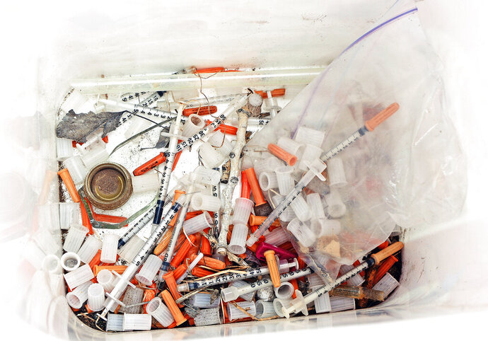 This May 8, 2019, photo shows hypodermic needles, needle caps, cotton swabs and other drug paraphernalia removed from Atrisco Park, home of the Atrisco Valley Little League, in Albuquerque, N.M. The little league park is fighting a battle against discarded syringes with attached hypodermic needles amid the region's outgoing opioid epidemic. (Jim Thompson/The Albuquerque Journal via AP)