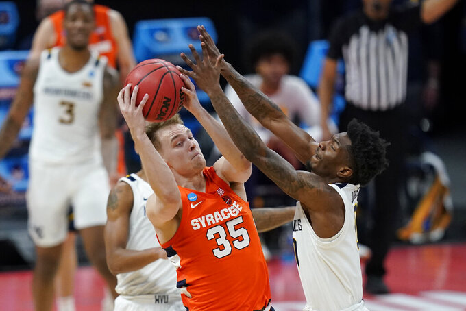 Syracuse's Buddy Boeheim (35) is fouled by West Virginia's Kedrian Johnson (0) during the second half of a second-round game in the NCAA men's college basketball tournament at Bankers Life Fieldhouse, Sunday, March 21, 2021, in Indianapolis. Syracuse defeated Syracuse 75-72. (AP Photo/Darron Cummings)