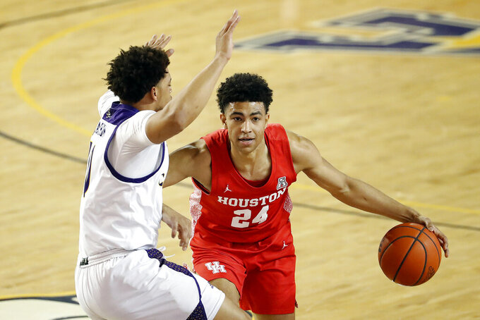 Houston's Quentin Grimes (24) drives the ball into East Carolina's Tyrie Jackson (10) during the first half of an NCAA college basketball game in Greenville, N.C., Wednesday, Feb. 3, 2021. (AP Photo/Karl B DeBlaker)
