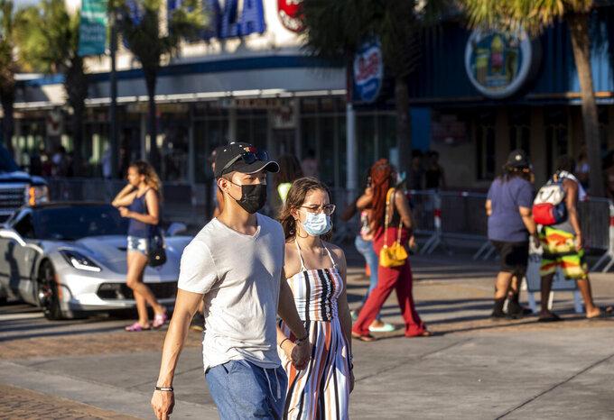 Tourists, some wearing masks, walk along Ocean Boulevard amid the coronavirus pandemic, Saturday, May 23, 2020, in Myrtle Beach, S.C. (Jason Lee/The Sun News via AP)