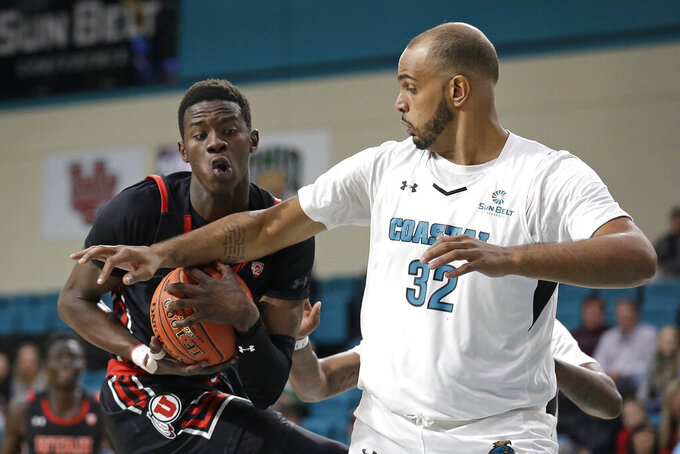 Utah center Lahat Thioune, left, carries the ball while Coastal Carolina center Levi Cook (32) defends during the first half of an NCAA college basketball game at the Myrtle Beach Invitational in Conway, S.C., Thursday, Nov. 21, 2019. (AP Photo/Gerry Broome)