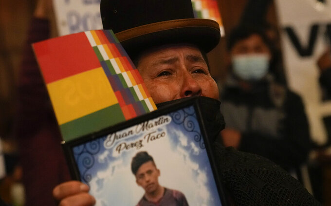 A woman holds a portrait of a relative who died in confrontations with security forces, during a presentation of an Independent Human Rights Experts' report regarding the political crisis and violence of 2019 that led to the fall of former President Evo Morales, in the Central Bank of Bolivia, in La Paz, Bolivia, Tuesday, Aug. 17, 2021. (AP Photo/Juan Karita)