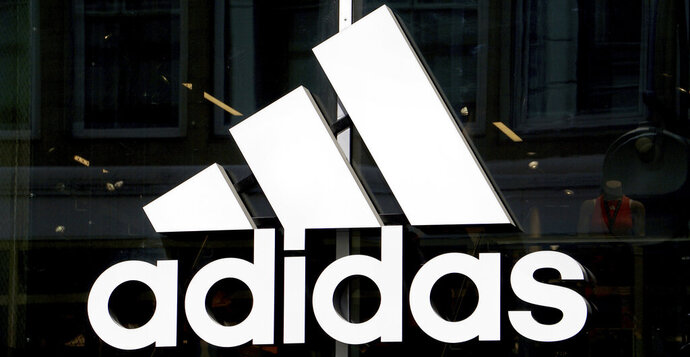 This May 6, 2019 photo shows the logo of the sports goods manufacturer Adidas in Berlin, Germany. The head of global human resources at sports apparel and shoe company Adidas resigned Tuesday, June 30, 2020 following criticism from employees of what they see as the company's failure to diversify its workforce. (AP Photo/Michael Sohn)