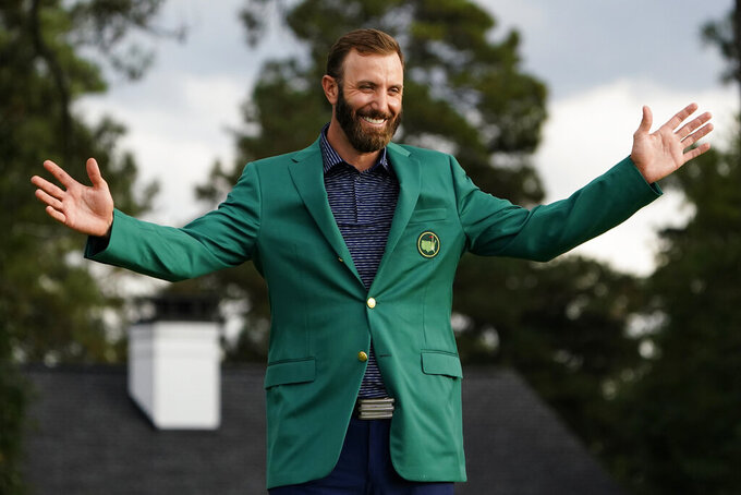 FILE - Masters golf champion Dustin Johnson shows off his green jacket after his victory in Augusta, Ga., in this Sunday, Nov. 15, 2020, file photo. Johnson was sure to send Phil Mickelson a text about his whereabouts next year the night of the champions dinner. (AP Photo/Matt Slocum, File)