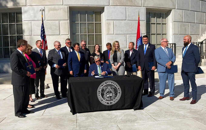 Missouri Gov. Mike Parson signs a copy of a bill limiting the duration of local public health orders during a ceremony Tuesday, June 15, 2021 outside the state Capitol in Jefferson City, Mo. Parson signed a couple dozen copies of the legislation and provided them to lawmakers and others who had supported the measure, including representatives of the restaurant industry. (AP Photo/David A. Lieb)
