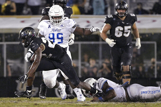 Central Florida running back Damarius Good (22) is tripped by Tulsa linebacker Treyvon Reeves (11) as defensive lineman Everitt Rogers (99) helps on the play during the second half of an NCAA college football game Saturday, Oct. 3, 2020, in Orlando, Fla. (AP Photo/Phelan M. Ebenhack)