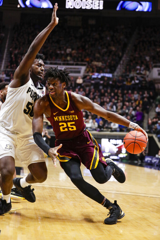 Minnesota center Daniel Oturu (25) drives around Purdue forward Trevion Williams (50) during the first half of an NCAA college basketball game in West Lafayette, Ind., Thursday, Jan. 2, 2020. (AP Photo/Michael Conroy)