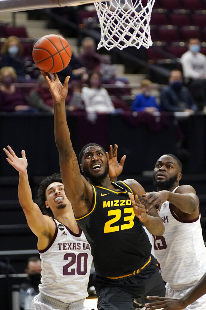 Missouri forward Jeremiah Tilmon (23) shoots past Texas A&M guard Andre Gordon (20) and forward Jonathan Aku (15) during the first half of an NCAA college basketball game Saturday, Jan. 16, 2021, in College Station, Texas. (AP Photo/Sam Craft)