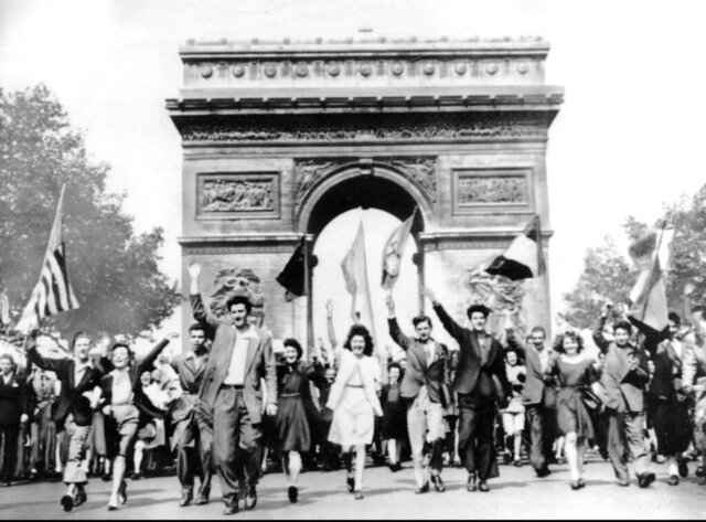FILE - In this May 8, 1945 file photo Parisians march through the Arc de Triomphe jubilantly waving flags of the Allied Nations as they celebrate the end of World War II in Europe. Nazi commanders signed their surrender to Allied forces in a French schoolhouse 75 years ago this week, ending World War II in Europe and the Holocaust. (AP Photo, File)