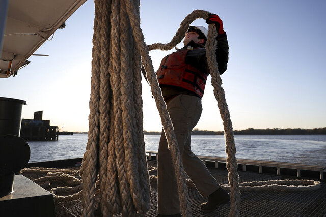 In this Nov. 13, 2019 photo, Alexey Bachmanov, who works for River Services, hangs up one of the ropes that keeps the tugboat against the dock in Philadelphia. His job, and thousands of others in Philadelphia and other waterfront cities revolve around the Delaware River, everything from canoe rentals to fishing guides to cargo shipping and handling. (David Maialetti/The Philadelphia Inquirer via AP)