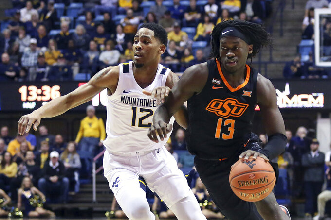 Oklahoma State guard Isaac Likekele (13) drives next to West Virginia guard Taz Sherman (12) during the first half of an NCAA college basketball game Tuesday, Feb. 18, 2020, in Morgantown, W.Va. (AP Photo/Kathleen Batten)