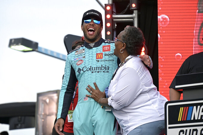 Driver Bubba Wallace, left, shares a laugh with Cheryl Ashley after Wendell Scott's family was presented a trophy before a NASCAR Cup Series auto race at Daytona International Speedway, Saturday, Aug. 28, 2021, in Daytona Beach, Fla. NASCAR presented Scott's family a custom trophy commemorating his historic 1963 victory. Scott was the only Black driver to win a race at NASCAR's top level. (AP Photo/Phelan M. Ebenhack)