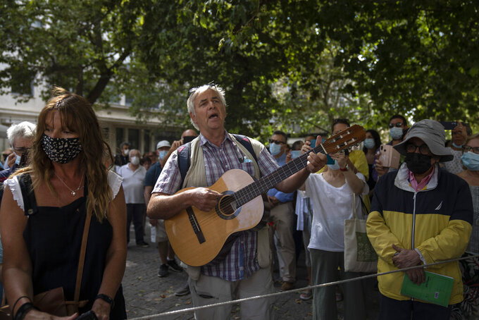 A man plays guitar outside the Athens Cathedral in Athens on Monday Sept. 6, 2021. Hundreds of people have gathered outside Athens Cathedral where Greek composer and politician Mikis Theodorakis is to lie in state in a chapel of the cathedral for three days ahead of his burial on the southern island of Crete. (AP Photo/Petros Giannakouris)