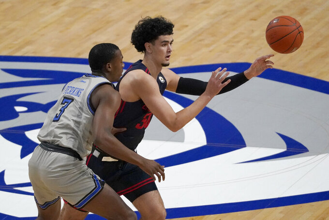 FILE - In this Jan. 26, 2021, file photo, Dayton's Mustapha Amzil, right, passes the ball as Saint Louis' Javonte Perkins (3) defends during the first half of an NCAA college basketball game in St. Louis. Amzil is among a small group of freshmen seizing an opportunity to play as midyear enrollees after the NCAA granted an extra year of eligibility to athletes in winter sports like basketball.  (AP Photo/Jeff Roberson, File)