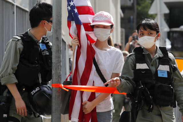 A protester carrying an American flag as she is stopped by riot police during a protest outside the U.S. Consulate in Hong Kong, Saturday, July 4, 2020 to mark the American Independence Day or