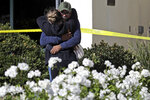 Mourners embrace outside the Thousand Oaks Teen Center, where relatives and friends gathered in the aftermath of a mass shooting, Thursday, Nov. 8, 2018, in Thousand Oaks, Calif. Multiple people were shot and killed late Wednesday by a gunman who opened fire at the Borderline Bar & Grill, which was holding a weekly country music dance night for college students. (AP Photo/Marcio Jose Sanchez)