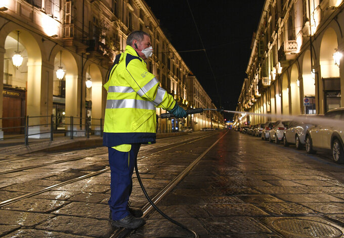 An operator sanitizes the streets in Turin, Italy, in the early hours of Saturday, March 14, 2020. A sweeping lockdown is in place in Italy to try to slow down the spread of coronavirus epidemic. For most people, the new coronavirus causes only mild or moderate symptoms. For some, it can cause more severe illness, especially in older adults and people with existing health problems.  (Fabio Ferrari/LaPresse via AP)