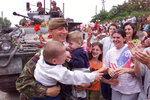 FILE - In this Sunday June 13, 1999 file photo, a British NATO soldier holds two ethnic Albanian children as the Albanian population of Pristina greet NATO troops as they enter various parts of the city. It's exactly 20 years since NATO forces set foot in the former Yugoslav province, after an allied bombing campaign ended Serbia's bloody crackdown on an insurrection by the majority ethnic Albanian population in Kosovo _ revered by Serbs as their historic and religious heartland. (AP Photo/Santiago Lyon, File)