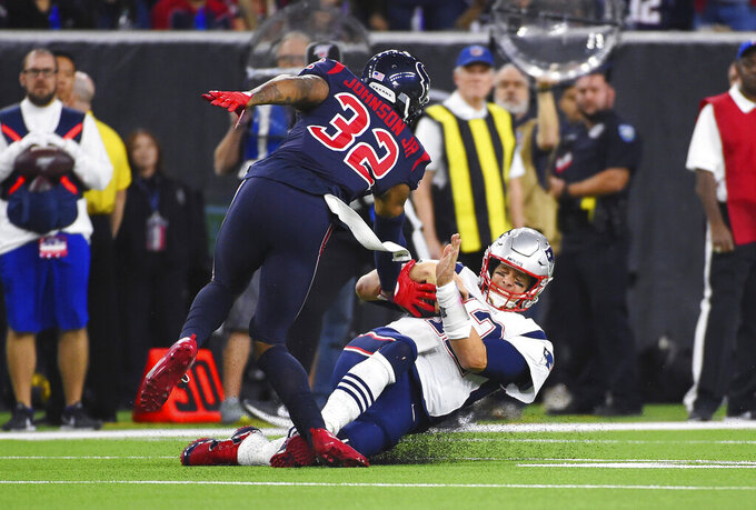 New England Patriots quarterback Tom Brady (12) slide into Houston Texans cornerback Lonnie Johnson (32) on a run during the first half of an NFL football game Sunday, Dec. 1, 2019, in Houston. (AP Photo/Eric Christian Smith)