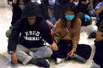 Protestors gather during a sit-in at a shopping mall to commemorate the four-month anniversary of an assault on commuters and protesters by armed men at a nearby train station in Hong Kong, Thursday, Nov. 21, 2019. A small but determined group of protesters remained holed up Thursday inside a Hong Kong university campus as the city's largest pro-Beijing political party urged voters to