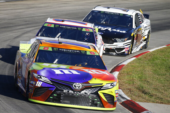 Kyle Busch (18), Denny Hamlin (11) and Aric Almirola (10) compete in the NASCAR Cup Series race at Martinsville Speedway in Martinsville, Va., Sunday, Oct. 27, 2019. (AP Photo/Steve Helber)