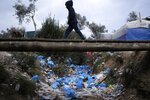 A migrant boy walks over discarded garbage outside the Moria refugee camp on the northeastern Aegean island of Lesbos, Greece, on Tuesday, Jan. 21, 2020, as some businesses and public services are holding a 24-hour strike to protest the migration situation. Thousands of migrants and refugees are stranded in massively overcrowded camps on the islands in increasingly precarious conditions. (AP Photo/Aggelos Barai)