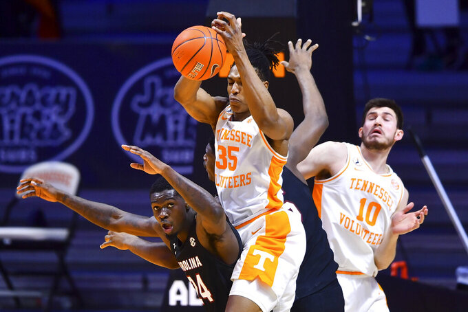 Tennessee's Yves Pons (35) attempts to get control of the ball over South Carolina's Keyshawn Bryant (24) during an NCAA college basketball game Wednesday, Feb. 17, 2021, in Knoxville, Tenn. (Brianna Paciorka/Knoxville News Sentinel via AP, Pool)
