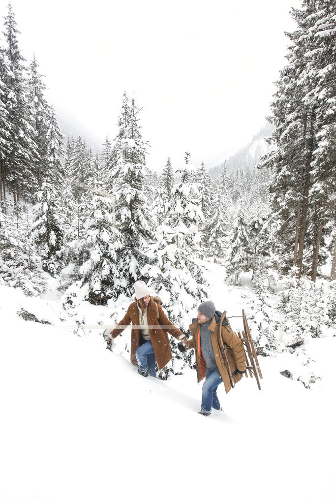 Young couple walking on snow during winter