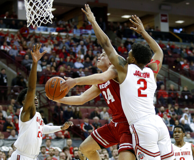 Wisconsin guard Brad Davison, center, goes up to shoot between Ohio State forward Andre Wesson, left, and guard Musa Jallow during the first half of an NCAA college basketball game in Columbus, Ohio, Sunday, March 10, 2019. (AP Photo/Paul Vernon)