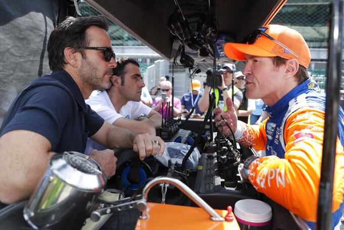 Scott Dixon, right, of New Zealand, talks with NASCAR driver Jimmy Johnson, left, and three-time Indy 500 champion Dario Franchitti, center, during practice for the Indianapolis 500 IndyCar auto race at Indianapolis Motor Speedway, Thursday, May 16, 2019 in Indianapolis. (AP Photo/Michael Conroy)