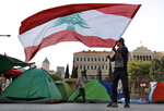 A protester waves the Lebanese flag during ongoing protests against the government, in front of the government palace, in Beirut, Thursday, Oct. 31, 2019. Lebanese security forces were still struggling to open some roads Thursday as protesters continued their civil disobedience campaign. (AP Photo/Bilal Hussein)