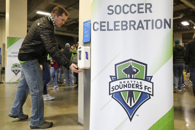 A man makes use of a hand-sanitizing station at CenturyLink Field prior to an MLS soccer match between the Seattle Sounders and the Chicago Fire, Sunday, March 1, 2020, in Seattle. Major North American professional sports leagues are talking to health officials and informing teams about the coronavirus outbreak. (AP Photo/Ted S. Warren)