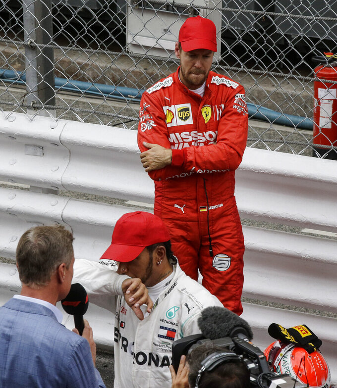 Second placed Ferrari driver Sebastian Vettel of Germany, up, reacts behind winner Mercedes driver Lewis Hamilton of Britain during the Monaco Formula One Grand Prix race, at the Monaco racetrack, in Monaco, Sunday, May 26, 2019. (AP Photo/Luca Bruno)