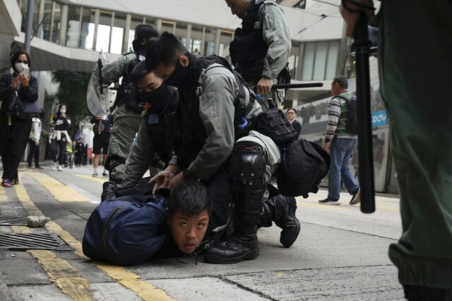 Riot police detain protesters calling for electoral reforms and a boycott of the Chinese Communist Party in Hong Kong, Sunday, Jan. 19, 2020. Hong Kong has been wracked by often violent anti-government protests since June, although they have diminished considerably in scale following a landslide win by opposition candidates in races for district councilors late last year. (AP Photo/Kin Cheung)