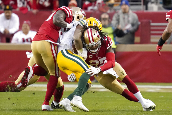 Green Bay Packers running back Aaron Jones, center, is tackled by San Francisco 49ers strong safety Jaquiski Tartt, left, and cornerback Richard Sherman during the first half of the NFL NFC Championship football game Sunday, Jan. 19, 2020, in Santa Clara, Calif. (AP Photo/Tony Avelar)
