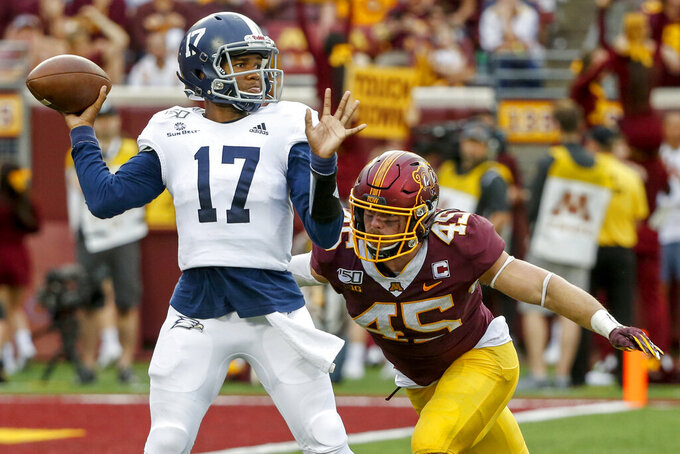 Georgia Southern quarterback Justin Tomlin (17) passes while under the pressure of Minnesota linebacker Carter Coughlin (45) in the fourth quarter of an NCAA college football game Saturday, Sept. 14, 2019, in Minneapolis. (AP Photo/Bruce Kluckhohn)