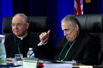 Cardinal Daniel DiNardo of the Archdiocese of Galveston-Houston, right, president of the United States Conference of Catholic Bishops, accompanied by Jose Gomez, archbishop of Los Angeles, make a gesture before the morning prayer during the United States Conference of Catholic Bishops (USCCB), 2019 Spring meetings in Baltimore, Tuesday, Jun 11, 2019. (AP Photo/Jose Luis Magana)
