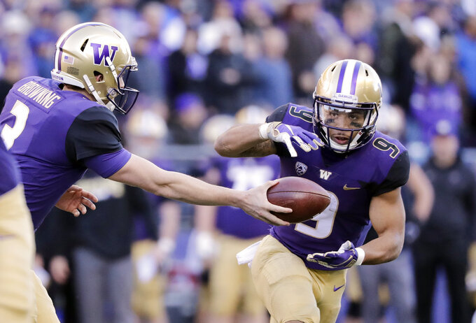 Washington quarterback Jake Browning, left, hands the ball off to Myles Gaskin in the first half of an NCAA college football game against Oregon State, Saturday, Nov. 17, 2018, in Seattle. (AP Photo/Elaine Thompson)