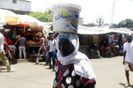 A woman balance a bucket in a local market in Conakry, Guinea, Thursday, Sept. 9, 2021. Guinea's new military leaders sought to tighten their grip on power after overthrowing President Alpha Conde, warning local officials that refusing to appear at a meeting convened Monday would be considered an act of rebellion against the junta. (AP Photo/ Sunday Alamba)