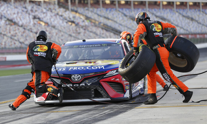 Crew members perform a pit stop on driver Martin Truex Jr's car during qualifying for Saturday's NASCAR All-Star Cup series auto race at Charlotte Motor Speedway in Concord, N.C., Friday, May 17, 2019. (AP Photo/Chuck Burton)