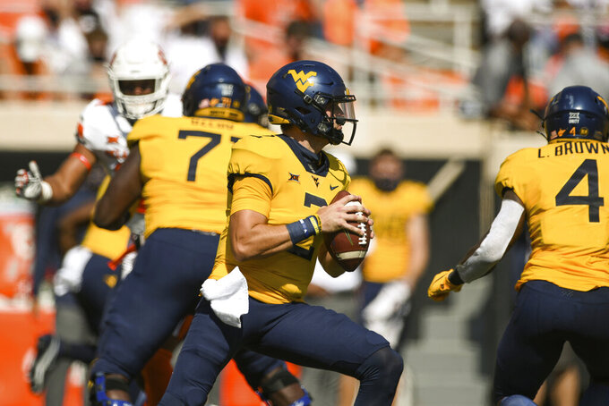 West Virginia quarterback Jarret Doege (2) looks for a receiver during the first half of the team's NCAA college football game against Oklahoma State on Saturday, Sept. 26, 2020, in Stillwater, Okla. (AP Photo/Brody Schmidt)