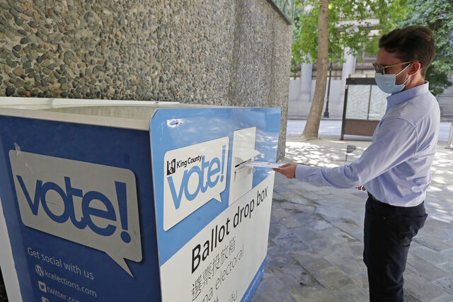 A person drops off a ballot for Washington state's primary election Tuesday, Aug. 4, 2020, at a collection box at the King County Administration Building in Seattle. Voters in the state have the option of voting by mail, depositing ballots in boxes, or seeking help in person for a missing ballot or other issues. (AP Photo/Ted S. Warren)